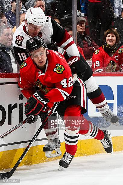 Gustav Forsling of the Chicago Blackhawks and Shane Doan of the Arizona Coyotes get physical by the glass in the first period at the United Center on...