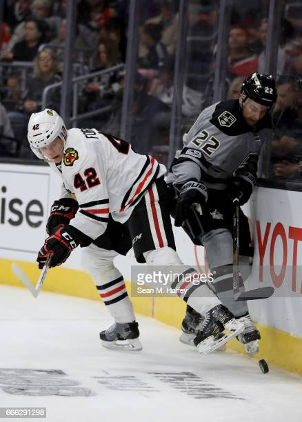 Gustav Forsling of the Chicago Blackhawks and Trevor Lewis of the Los Angeles Kings battle for a loose puck during the second period of a game at...