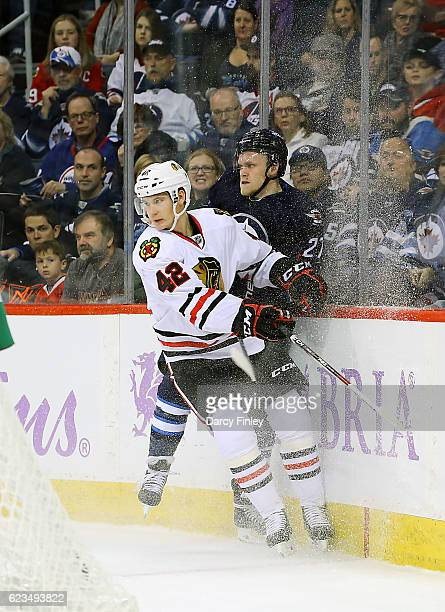 Gustav Forsling of the Chicago Blackhawks checks Nikolaj Ehlers of the Winnipeg Jets into the boards during first period action at the MTS Centre on...