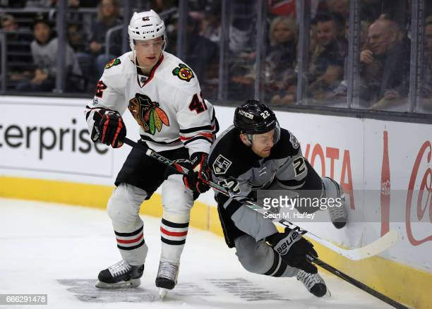 Gustav Forsling of the Chicago Blackhawks pushes Trevor Lewis of the Los Angeles Kings into the boards during the second period of a game at Staples...