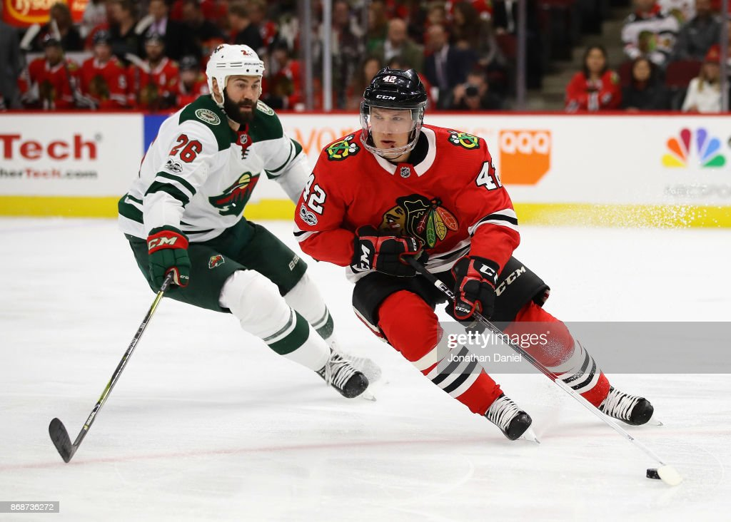 Gustav Forsling #42 of the Chicago Blackhawks turns with the puck in front of Daniel Winnik #26 of the Minnesota Wild at the United Center on October 12, 2017 in Chicago, Illinois.