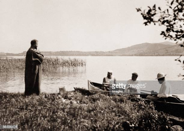 Gustav Klimt in a gown at the Attersee standing at the shore three friends in a rowboat at the Attersee Photography around 1910 [Gustav Klimt im...