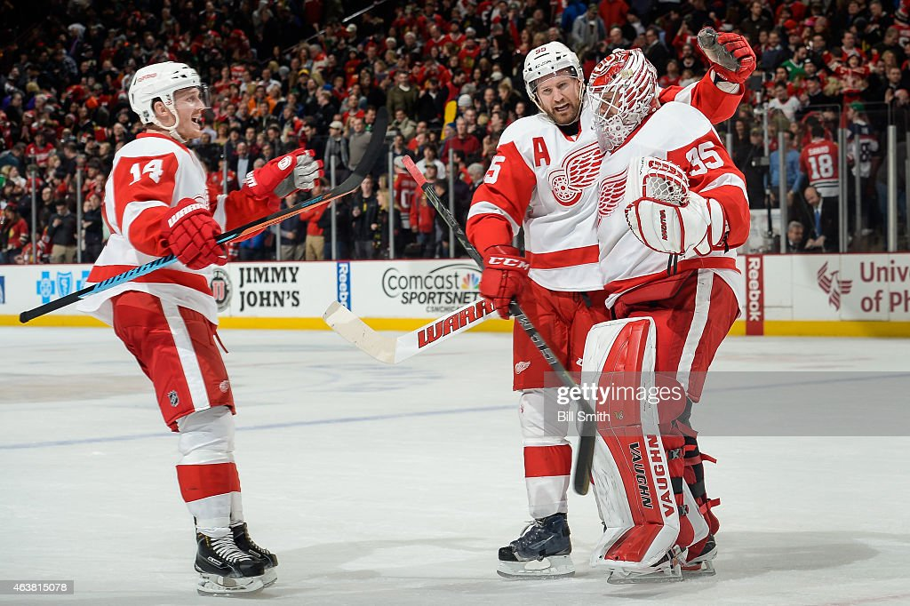 Gustav Nyquist #14 and Niklas Kronwall #55 celebrate with goalie Jimmy Howard #35 of the Detroit Red Wings after defeating the Chicago Blackhawks 3-2 during the NHL game at the United Center on February 18, 2015 in Chicago, Illinois.