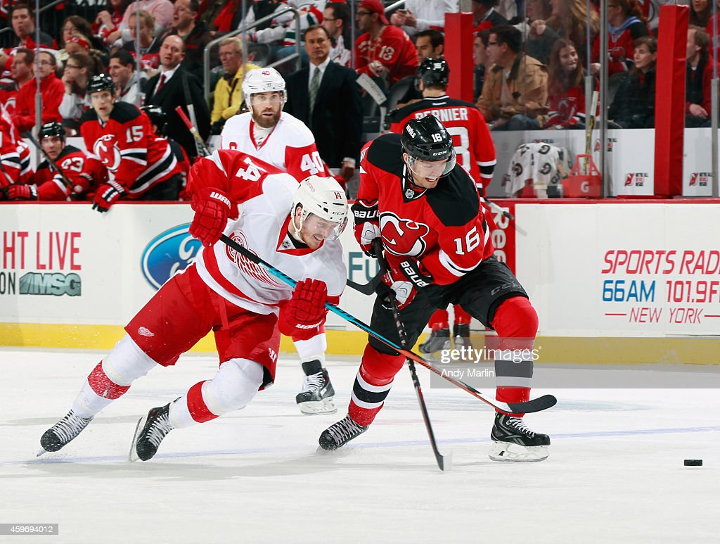 Gustav Nyquist #14 of the Detroit Red Wings and Jacob Josefson #16 of the New Jersey Devils battle for a loose puck during the game at the Prudential Center on November 28, 2014 in Newark, New Jersey.