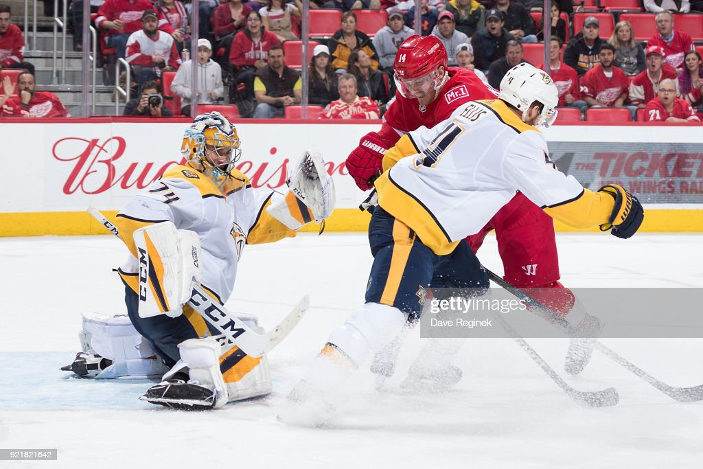 Gustav Nyquist #14 of the Detroit Red Wings battles in front of the goaltender Juuse Saros #74 of the Nashville Predators with Ryan Ellis #4 of the Predators during an NHL game at Little Caesars Arena on February 20, 2018 in Detroit, Michigan. The Predators defeated the Wings 3-2.