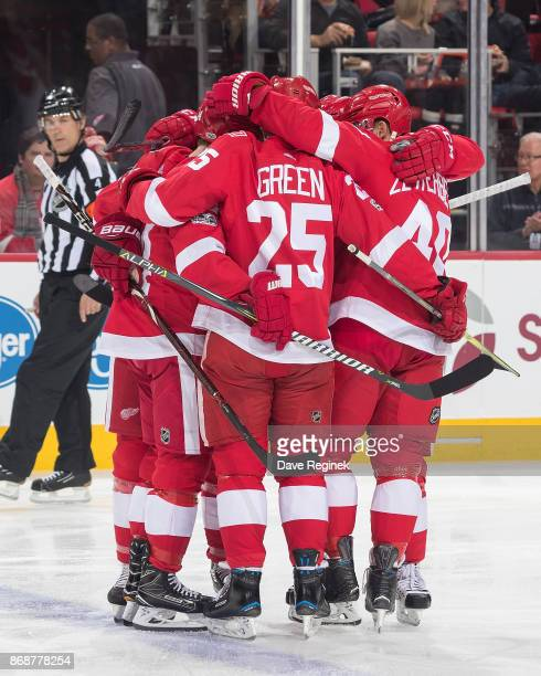 Gustav Nyquist of the Detroit Red Wings celebrates his first period goal with teammates Mike Green and Henrik Zetterberg during an NHL game against...