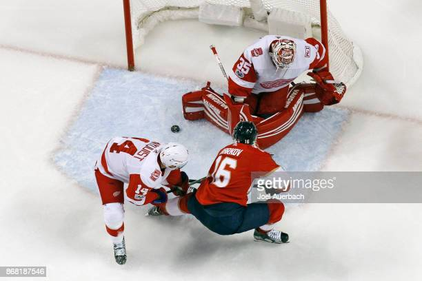 Gustav Nyquist of the Detroit Red Wings defends against Aleksander Barkov of the Florida Panthers as Goaltender Jimmy Howard stops his shot at the...