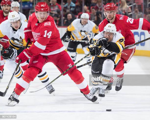 Gustav Nyquist of the Detroit Red Wings skates after a loose puck in front of Patric Hornqvist of the Pittsburgh Penguins during an NHL game at...