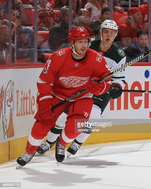 Gustav Nyquist of the Detroit Red Wings skates behind the net followed by Joel Eriksson Ek of the Minnesota Wild during the first ever NHL game at...