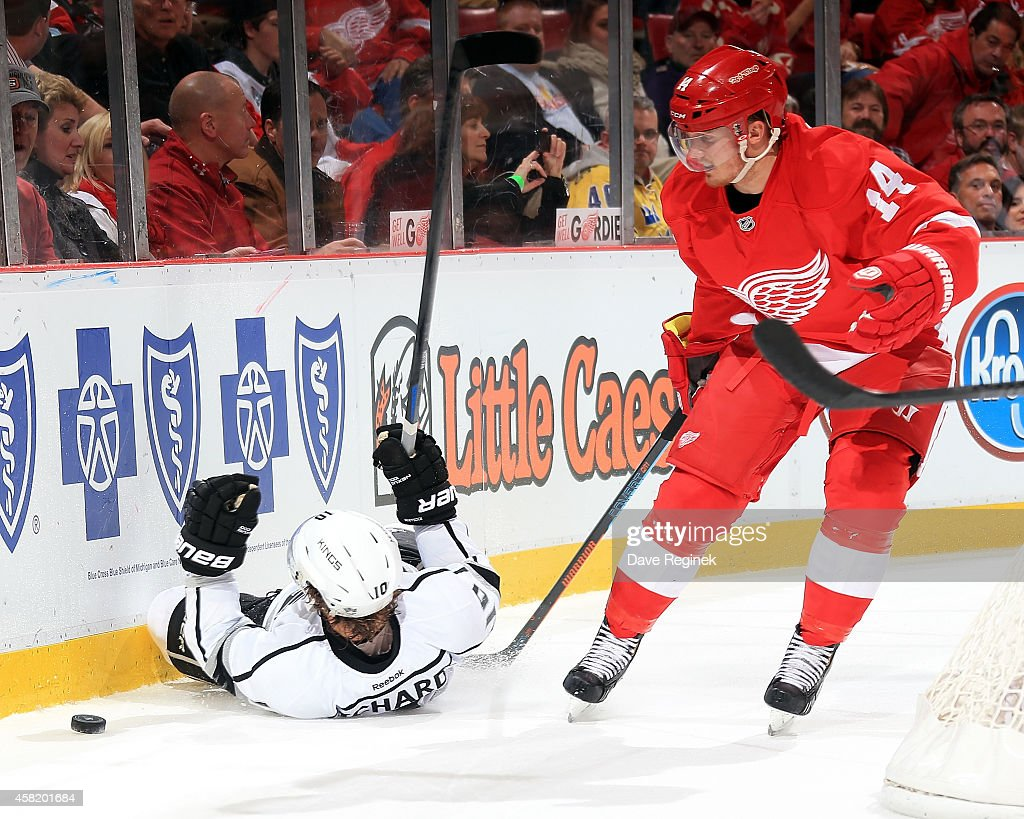 Gustav Nyquist #14 of the Detroit Red Wings trips Mike Richards #10 of the Los Angeles Kings in the second period during a NHL game on October 31, 2014 at Joe Louis Arena in Detroit, Michigan.
