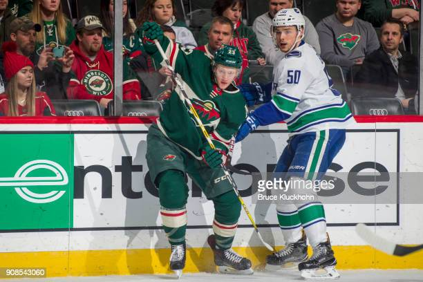 Gustav Olofsson of the Minnesota Wild and Brendan Gaunce of the Vancouver Canucks skate to the puck during the game at the Xcel Energy Center on...