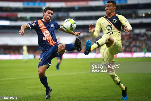 Gustavo Alustiza of Puebla struggles for the ball with Luis Reyes of America during a 10th round match between America and Puebla as part of Torneo...