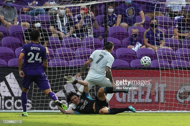 Gustavo Bou of New England Revolution scores a goal past Brian Rowe of Orlando City SC and Kyle Smith of Orlando City SC during the MLS Eastern...