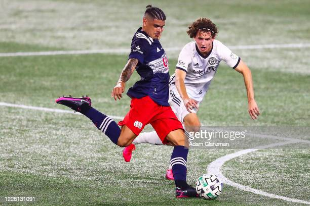 Gustavo Bou of New England Revolution shoots the ball while guarded by Brenden Aaronson of Philadelphia Union during a game at Gillette Stadium on...