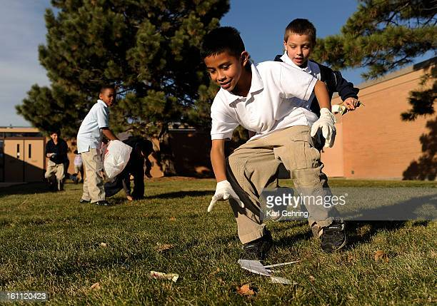 Gustavo Cordero age 8 center and Delano Arias age 9 right raced to pick up scraps of paper outside school Friday during a trash treasure hunt About...