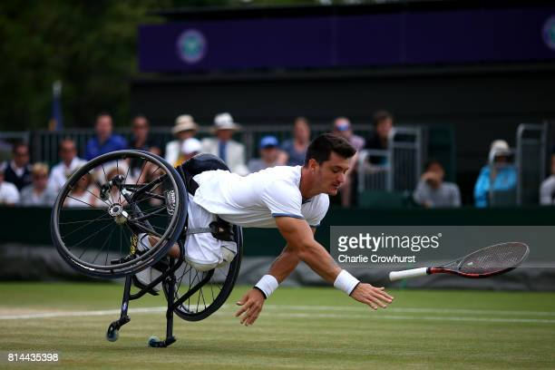 Gustavo Fernandez of Argentina falls over as he reaches for a shot during his Gentlemen's wheel chair tennis semi final against Alfie Hewett of Great...