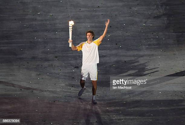 Gustavo Kuerten carries the Olympic flame through the stadium during The 2016 Summer Olympics Opening Ceremony at Maracana Stadium on August 5 2016...