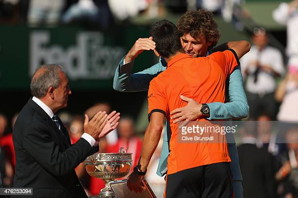 Gustavo Kuerten presents Novak Djokovic of Serbia with the runners up trophy after his defeat by Stanislas Wawrinka of Switzerland in the Men's...