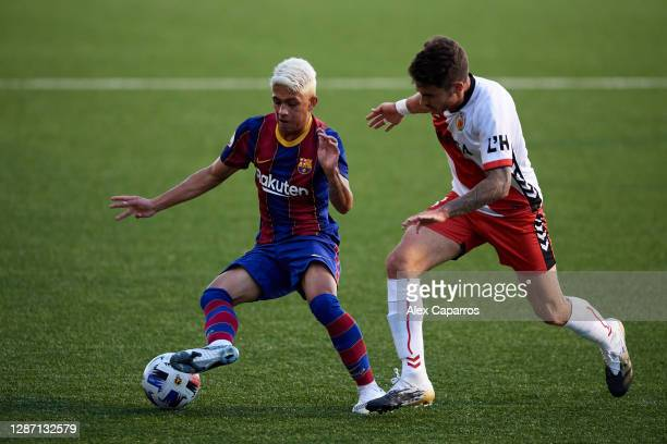 Gustavo Maia of FC Barcelona B battles for the ball with Adria Parera of CE L'Hospitalet during the Segunda Division B Group IIIA match between CE...