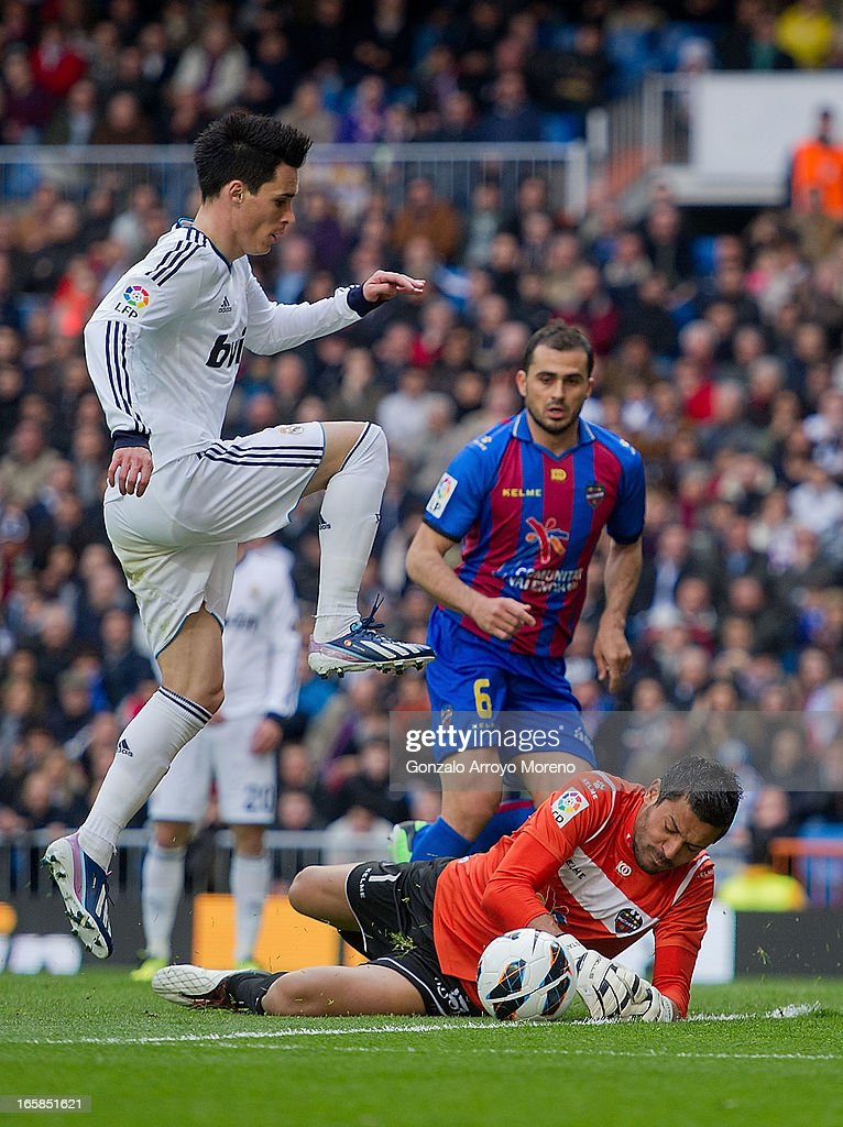 Gustavo Munua (R) of Levante UD tries to stop a shooting of Jose Maria Callejon (L) of Real Madrid CF during the La Liga match between Real Madrid CF and Levante UD at Santiago Bernabeu Stadium on April 6, 2013 in Madrid, Spain.