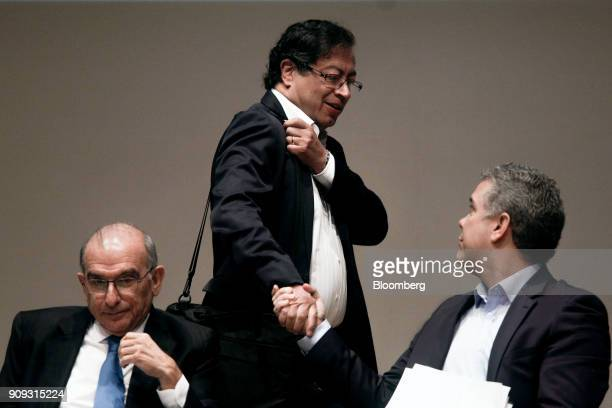 Gustavo Petro presidential candidate for the Progressivists Movement Party center shakes hands with Ivan Duque presidential candidate for the...