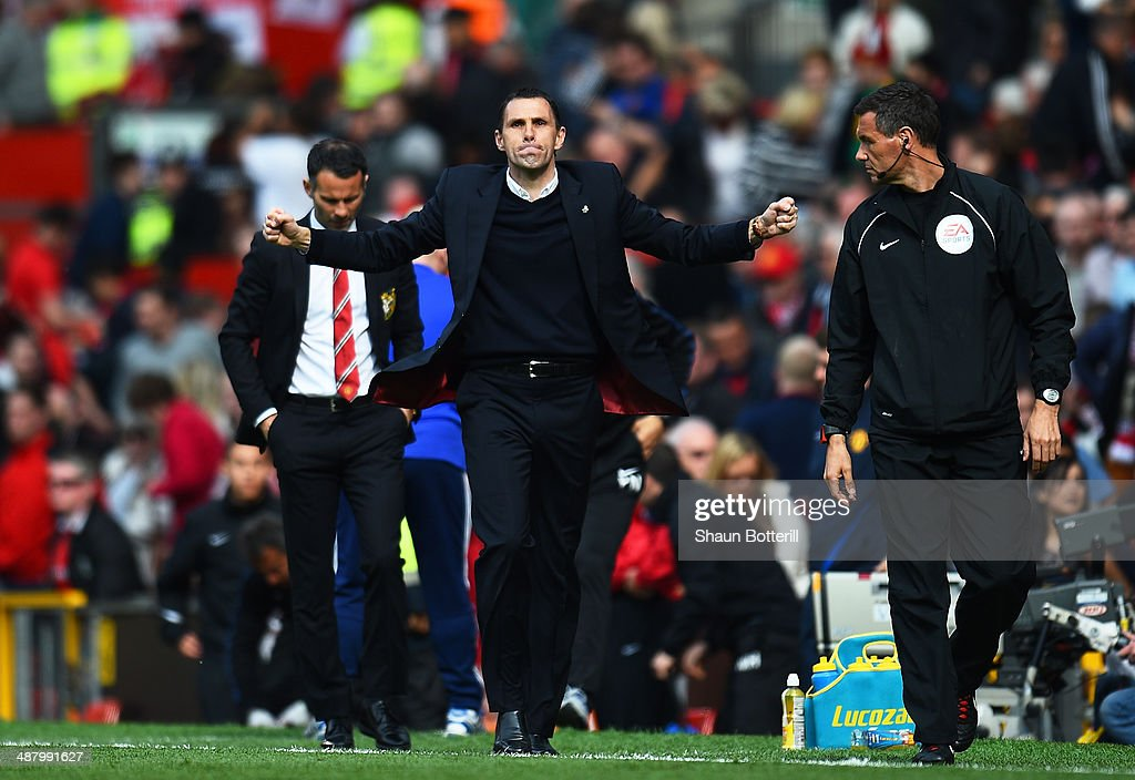 Gustavo Poyet the Sunderland manager celebrates his team's 1-0 victory as a dejected Ryan Giggs the Manchester United interim manager walks behind during the Barclays Premier League match between Manchester United and Sunderland at Old Trafford on May 3, 2014 in Manchester, England.
