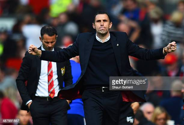 Gustavo Poyet the Sunderland manager celebrates his team's 1-0 victory as a dejected Ryan Giggs the Manchester United interim manager walks behind...