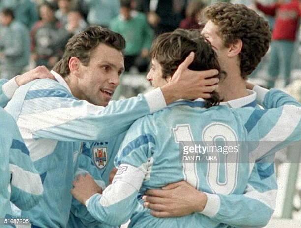 Gustavo Poyet y Alvaro Gutierrez saludan a Enzo Francescoli autor del gol uruguayo el 09 Julio durante el partido en el que Uruguay vencio 10 a...