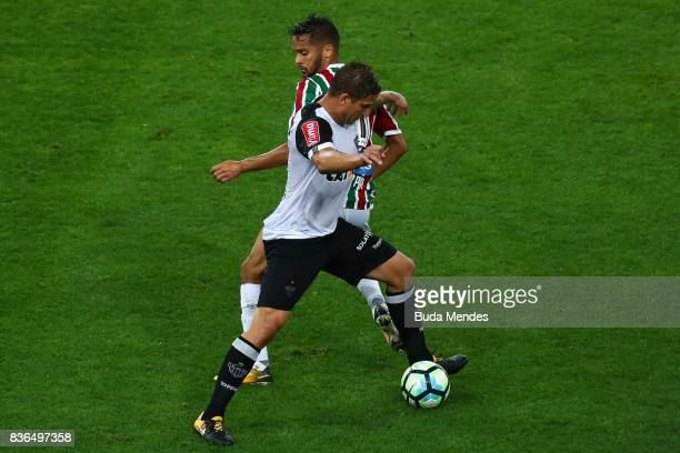 Gustavo Scarpa of Fluminense struggles for the ball with Rafael Moura of Atletico MG during a match between Fluminense and Atletico MG part of...