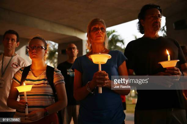 Guwendolyn Field Regina Sondej and Sal Cuccia attend a candle light vigil at Florida Atlantic University for the 17 people killed during a shooting...