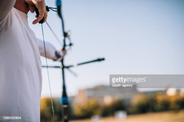 guy aiming at target - curved arrows stock photos and pictures