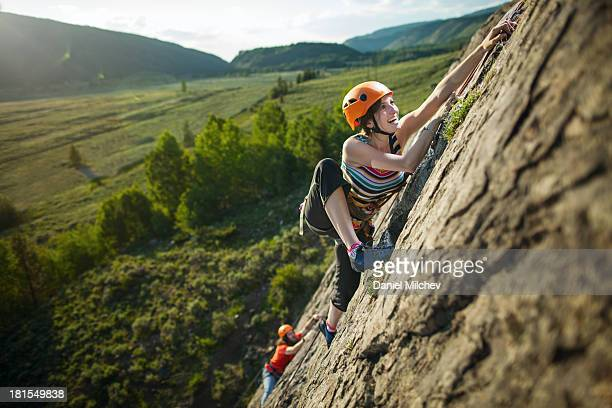 guy and a girl, rock climbing during sunset. - scalare foto e immagini stock