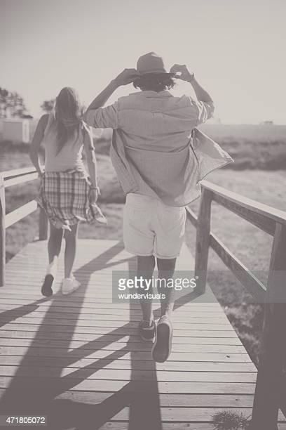 Ragazzo e ragazza cammina lungo pontile in legno nel giorno d'estate