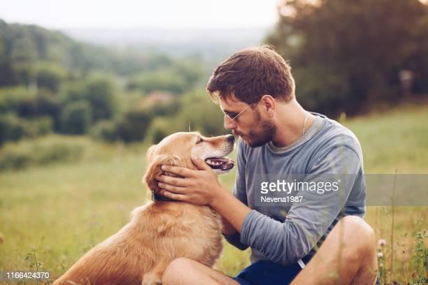 guy and his dog having a fun in the nature - faccia a faccia foto e immagini stock