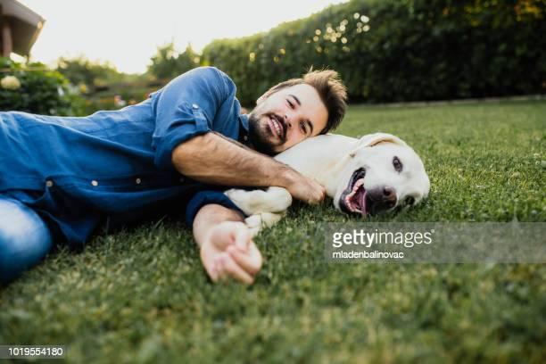 guy and his dog, labrador retriever, courtyard - labrador retriever stock photos and pictures