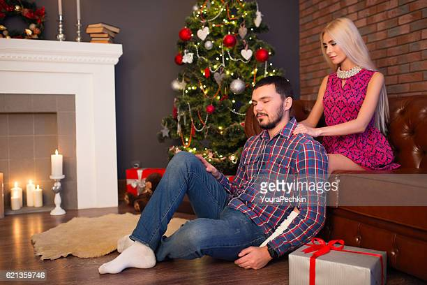 Guy and his girl with gift near the Christmas tree