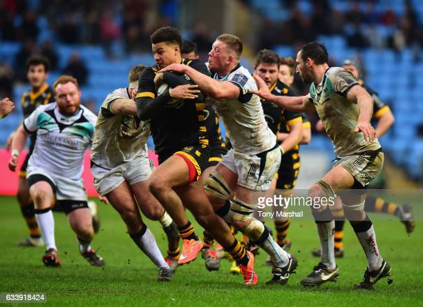 Guy Armitage of Wasps is tackled by Lloyd Ashley of Ospreys during the AngloWelsh Cup match between Wasps and Ospreys at The Ricoh Arena on February...