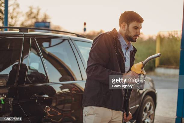 guy at the gas station - refuelling stock pictures, royalty-free photos & images