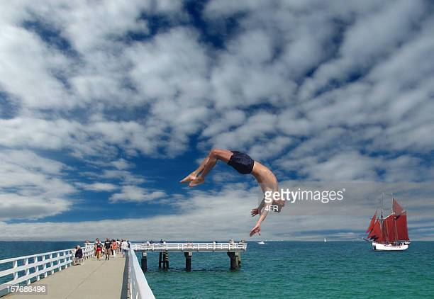 Guy backflipping off a pier