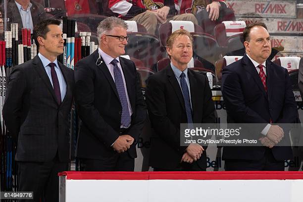 Guy Boucher Marc Crawford Rob Cookson and Martin Raymond of the Ottawa Senators look from the bench during player introductions prior to their home...