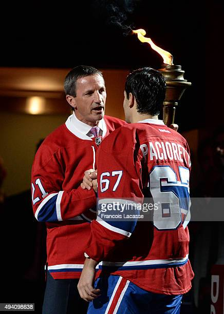 Guy Carbonneau hands over the flame to Carey Price of the Montreal Canadiens during the pre game ceremony prior to the NHL game against the New York...