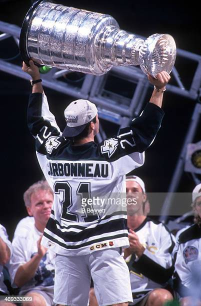 Guy Carbonneau of the Dallas Stars holds aloft the Stanley Cup Trophy during the Stars parade after they defeated the Buffalo Sabres in six games to...
