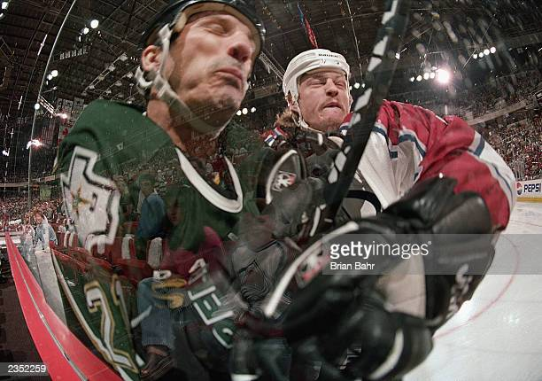 Guy Carbonneau of the Dallas Stars left is smashed to the glass by Aaron Miller of the Colorado Avalanche during their West Conference Finals game at...
