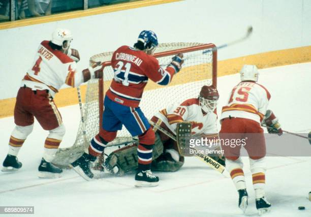 Guy Carbonneau of the Montreal Canadiens goes for the rebound as goalie Mike Vernon of the Calgary Flames hits the puck away from the net as he gets...