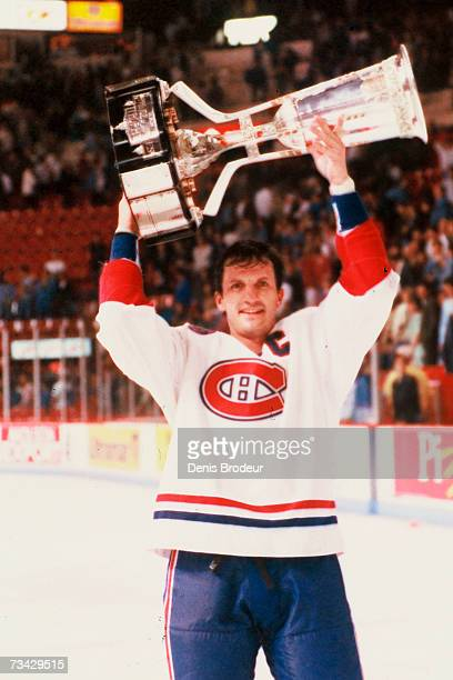 Guy Carbonneau of the Montreal Canadiens hoists the Prince of Wales Trophy over his head after defeating the Los Angeles Kings in the Stanley Cup...