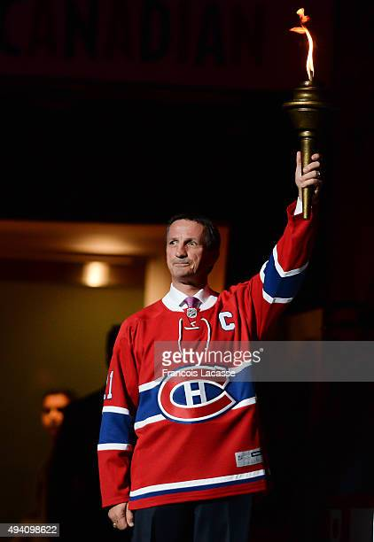 Guy Carbonneau of the Montreal Canadiens holds the flame during the pre game ceremony prior to the NHL game against the New York Rangers at the Bell...