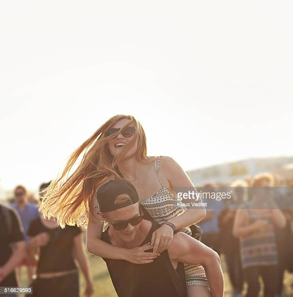 Guy carrying girlfriend at outside festival