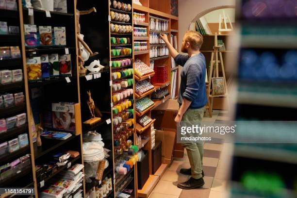 近代的な店で塗料を選択する男 - アクリル ストックフォトと画像