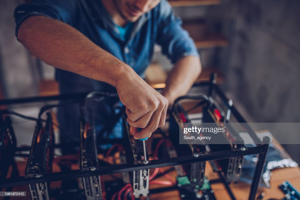Guy configures the computer for mining cryptocurrency : Stock Photo