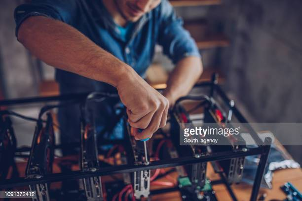 guy configures the computer for mining cryptocurrency - cryptocurrency mining stock pictures, royalty-free photos & images